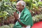 Bharatiya Janata Party (BJP) leader B. S. Yeddyurappa greets people as he walks to be sworn as Chief Minister of Karnataka state in Bangalore, India, Thursday, May 17, 2018. The elections in India's southern state of Karnataka were held on last Saturday. (AP Photo/Aijaz Rahi)
