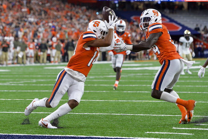 Syracuse defensive back Jason Simmons, left, intercepts a deflected pass as defensive back Eric Coley reaches for the ball during the first half of an NCAA college football game against Wake Forest in Syracuse, N.Y., Saturday, Oct. 9, 2021. (AP Photo/Adrian Kraus)