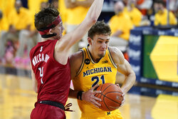 Michigan Wolverines guard Franz Wagner (21) drives on Rutgers guard Paul Mulcahy (4) in the first half of an NCAA college basketball game in Ann Arbor, Mich., Thursday, Feb. 18, 2021. (AP Photo/Paul Sancya)