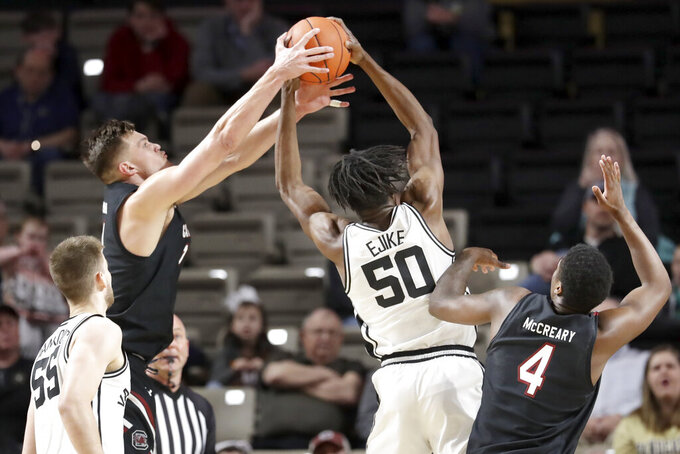 South Carolina's Maik Kotsar, reaches for a rebound with Vanderbilt's Ejike Obinna (50) in the first half of an NCAA college basketball game Saturday, March 7, 2020, in Nashville, Tenn. (AP Photo/Mark Humphrey)