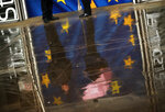 People and an European Union flags are reflected on the ground on a rainy day outside the European Commission headquarters in Brussels, Thursday, March 14, 2019. Britons in Brussels are fretting about how their country's looming departure will affect their daily lives. Growing numbers are taking Belgian nationality as a way of ensuring they can still live, work and travel freely in Europe after Brexit. (AP Photo/Francisco Seco)