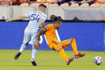 Houston Dynamo forward Maximiliano Urruti, right, falls into Sporting Kansas City midfielder Remi Walter (54) as they chase the ball during the first half of an MLS soccer match Wednesday, May 12, 2021, in Houston. (AP Photo/Michael Wyke)