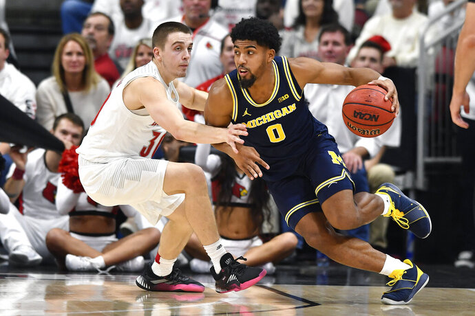 Michigan guard David DeJulius (0) attempts to drive past the defense of Louisville guard Ryan McMahon (30) during the second half of an NCAA college basketball game in Louisville, Ky., Tuesday, Dec. 3, 2019. Louisville won 58-43. (AP Photo/Timothy D. Easley)