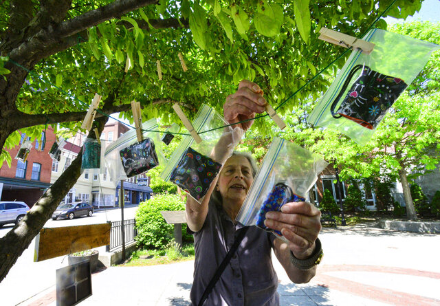 Deborah Casdin, of Brattleboro, Vt., takes a face mask that was hanging from a tree in Pliny Park, in Brattleboro, on Tuesday, May 26, 2020. A sign on the tree encouraged people to take a free mask to help out during the COVD-19 pandemic. (Kristopher Radder/ Brattleboro Reformer via AP)