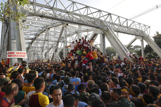 A crowd of Filipino Roman Catholic devotees try to climb the carriage of the Black Nazarene during a raucous procession to celebrate its feast day Thursday, Jan. 9, 2020, in Manila, Philippines. A mammoth crowd of mostly barefoot Filipino Catholics prayed for peace in the increasingly volatile Middle East at the start Thursday of an annual procession of a centuries-old black statue of Jesus Christ in one of Asia's biggest religious events. (AP Photo/Aaron Favila)
