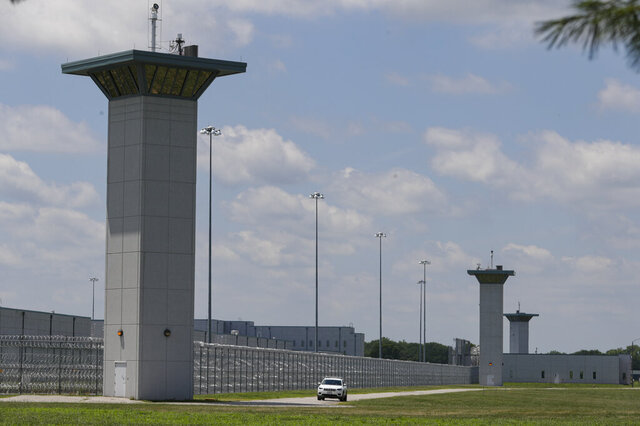 FILE - In this July 17, 2020, file photo the federal prison complex in Terre Haute, Ind., is shown. Indiana State Police agreed Friday, Aug. 14, 2020 to stop blocking roads to the prison where federal executions resumed last month and are set to continue, backing down after anti-death penalty activists said in a lawsuit the roadblocks impeded their speech rights. (AP Photo/Michael Conroy, File)