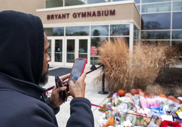 Michael Briggs of Philadelphia takes a photo at a small memorial left in remembrance to Kobe Bryant at the entrance of the Bryant Gymnasium at Lower Merion High School, Monday, Jan. 27, 2020, in Wynnewood, Pa.  The 41-year-old Bryant and his 13-year-old daughter, Gianna, were among nine people who died in the crash in Calabasas in foggy weather conditions Sunday morning. (AP Photo/Chris Szagola)