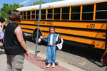 Mimi, 8, greets her mother Dawn Lourenco after getting off a school bus on Friday, Sept. 3, 2021, in Albuquerque, N.M. Lourenco's two other children were forced to learn remotely due to outbreaks in their schools. (AP Photo/Cedar Attanasio)