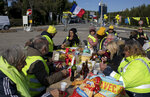 Yellow vest  demonstrators enjoy a lunch to celebrate the one-year anniversary of the national yellow vest movement, at a traffic circle in La Ciotat, southern France, Saturday, Nov. 17, 2019.  Some protests have clashed with police as yellow vest protesters are marking a year of protests, seeking what they see as economic justice for the French people with changes in government policies.(AP Photo/Daniel Cole)