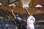 Nicholls State forward Elvis Harvey Jr. (23) goes to make a shot as he is defended by West Virginia forward Oscar Tshiebwe (34) during the first half of an NCAA college basketball game Saturday, Dec. 14, 2019, in Morgantown, W.Va. (AP Photo/Kathleen Batten)