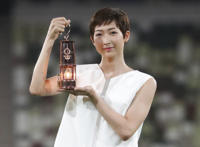 FILE - In this July 23, 2020, file photo, Japanese swimming athlete Rikako Ikee holding the lantern containing Olympic flame poses during a photo session at the Olympic Stadium in Tokyo. Japanese swim sta Ikee will compete on Saturday, Aug. 29, in a meet for the first time since being treated for leukemia. Ikee won six gold medals in the Asian Games two years ago in Jakarta, Indonesia, and would have been a favorite in several events going into the now-postponed Tokyo Olympics.  (Du Xiaoyi/Pool Photo via AP, File)