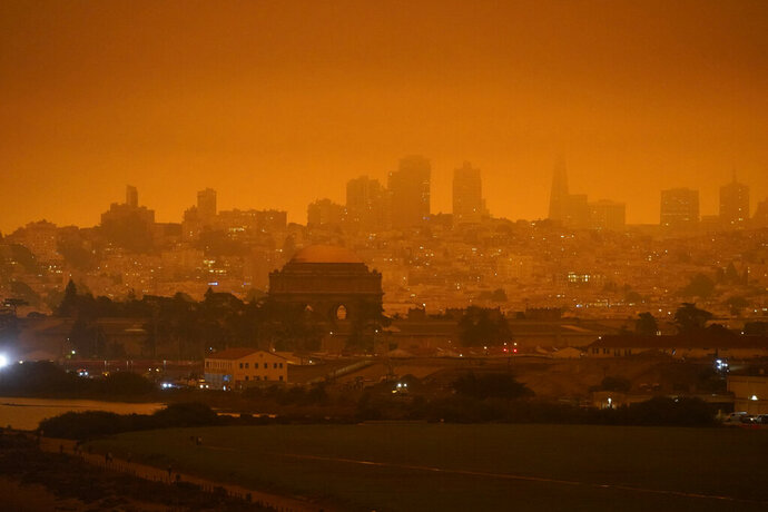FILE - In this Sept. 9, 2020, file photo, taken at 11:18 a.m., is a dark orange sky above Crissy Field and the city caused by heavy smoke from wildfires in San Francisco. Wildfires that scorched huge swaths of the West Coast churned out massive plumes of choking smoke that blanketed millions of people with hazardous pollution that spiked emergency room visits and that experts say could continue generating health problems for years. An Associated Press analysis of air quality data shows 5.2 million people in five states were hit with hazardous levels of pollution for at least a day. (AP Photo/Eric Risberg, File)