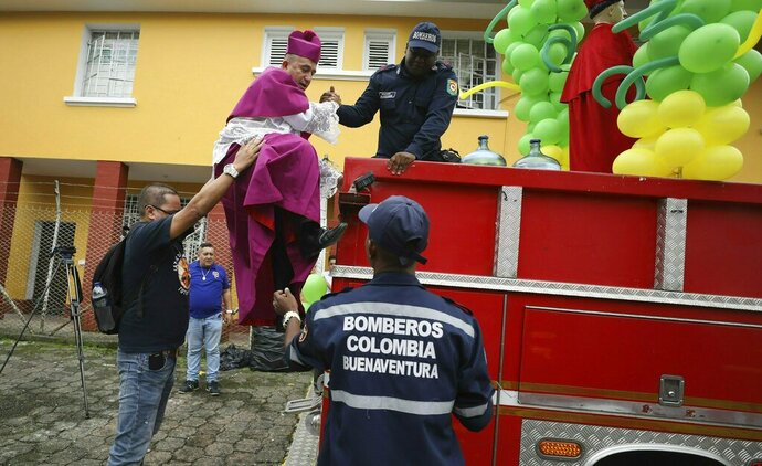 Catholic Bishop Ruben Dario Jaramillo Montoya is helped onto a fire truck in Buenaventura, Colombia, Saturday, July 13, 2019. Jaramillo traveled on the fire truck to some of Buenaventura's most crime-ridden neighborhoods on Saturday, sprinkling water that he had blessed in what he called an attempt to thwart drug trafficking gangs and other illegal groups. (AP Photo/Fernando Vergara)