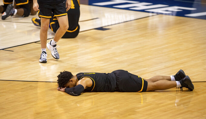 Appalachian State guard Justin Forrest (1) lies on the floor after his team's loss to Norfolk State in a First Four game in the NCAA men's college basketball tournament, Thursday, March 18, 2021, in Bloomington, Ind. (AP Photo/Doug McSchooler)