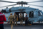In this photo provided by the U.S. Navy, sailors assigned to an explosive ordnance unit board an MH-60S Seahawk helicopter on the flight deck of aircraft carrier USS Ronald Reagan to head to an oil tanker that was attacked off the coast of Oman in the Arabian Sea on Friday, July 30, 2021. An attack on an oil tanker linked to an Israeli billionaire killed two crew members off Oman in the Arabian Sea, authorities said Friday, marking the first fatalities after years of assaults targeting shipping in the region. (Mass Communication Specialist 2nd Class Quinton A. Lee/U.S. Navy, via AP)