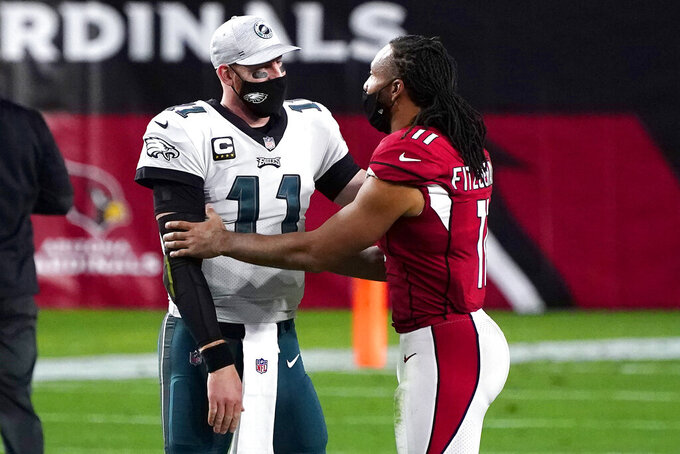 Arizona Cardinals wide receiver Larry Fitzgerald, greets Philadelphia Eagles quarterback Carson Wentz after an NFL football game, Sunday, Dec. 20, 2020, in Glendale, Ariz. The Cardinals won 33-26. (AP Photo/Rick Scuteri)