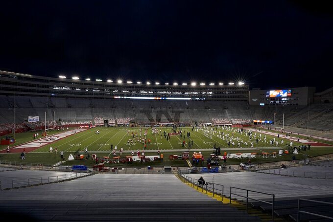 The seats at Camp Randall Stadium are empty as players warm up before an NCAA college football game between Wisconsin and Illinois Friday, Oct. 23, 2020, in Madison, Wis. (AP Photo/Morry Gash)