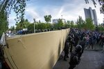 Demonstrators gather in front of a new builded fence blocked by police, to protest plans to construct a cathedral in a park in Yekaterinburg, Russia, Wednesday, May 15, 2019. Hundreds of riot police have surrounded a park in Russia's fourth-largest city before what's expected to be a third consecutive day of protests against building a new cathedral. (AP Photo/Anton Basanayev)