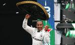 ARCHIVO - En imagen de archivo del domingo 27 de octubre de 2019, el piloto británico Lewis Hamilton, de Mercedes, arroja un sombrero de charro al público mientras festeja su victoria en el Gran Premio de México de la Fórmula Uno, en el autódromo Hermanos Rodríguez de la capital mexicana. (AP Foto/Rebecca Blackwell, archivo)