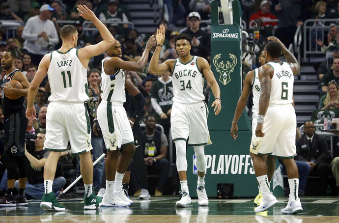 Milwaukee Bucks' Giannis Antetokounmpo gives high-fives to his teammates during the first half of Game 2 of an NBA basketball first-round playoff series against the Detroit Pistons on Wednesday, April 17, 2019, in Milwaukee. (AP Photo/Aaron Gash)