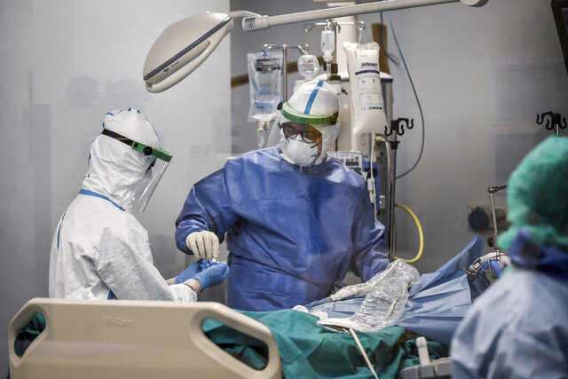 In this photograph taken from behind a window, doctors work on a Covid-19 patient in the intensive care unit of San Matteo Hospital, in Pavia, northern Italy, Thursday, March 26, 2020. The San Matteo hospital is where Patient 1, a 38-year-old Unilever worker named Mattia, was kept since he tested positive for Covid-19 on Feb. 21 and opened Italy's health care crisis. The new coronavirus causes mild or moderate symptoms for most people, but for some, especially older adults and people with existing health problems, it can cause more severe illness or death. (Claudio Furlan/LaPresse via AP)