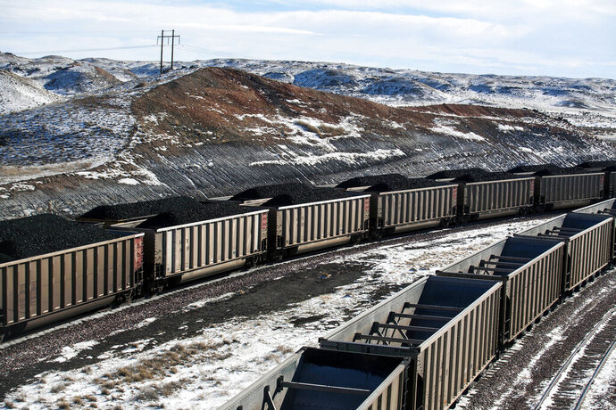 FILE - In this Jan. 9, 2014, file photo, rail cars are filled with coal and sprayed with a topper agent to suppress dust at Cloud Peak Energy's Antelope Mine north of Douglas, Wyo. A judge approved a bankruptcy reorganization for one of the biggest U.S. coal companies Thursday, Dec. 5, 2019 amid ongoing uncertainty about how its mines will be bonded in the long term. (Ryan Dorgan/The Casper Star-Tribune via AP, File)