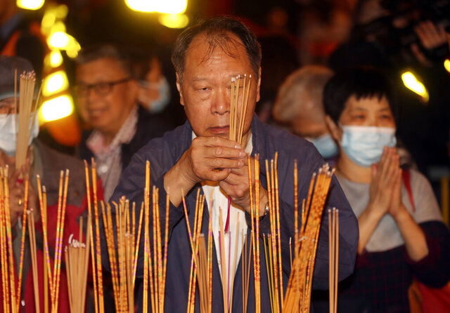 A man burn joss sticks as he prays at the Wong Tai Sin Temple, Friday, Jan. 24, 2020, in Hong Kong, to celebrate the Lunar New Year which marks the Year of the Rat in the Chinese zodiac. China is expanding its lockdown against the deadly new virus to an unprecedented 36 million people and rushing to build a prefabricated, 1,000-bed hospital for victims as the outbreak cast a pall over Lunar New Year, the country's biggest and most festive holiday. (AP Photo/Achmad Ibrahim)