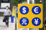 People wearing face masks walk by signs of foreign currency outside a money exchange office at a shopping district in Seoul, South Korea, Thursday, Aug. 12, 2021. Asian shares were mixed Thursday as caution set in among investors following another wobbly day of trading on Wall Street.   (AP Photo/Lee Jin-man)
