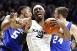 Xavier's Quentin Goodin (3) reacts after pulling in a rebound against Creighton's Ty-Shon Alexander (5) during overtime of an NCAA college basketball game Wednesday, Feb. 13, 2019, in Cincinnati. (AP Photo/John Minchillo)