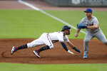 Atlanta Braves' Dansby Swanson, left, dives back to first base ahead of the throw to New York Mets first baseman Pete Alonso, right, in the second inning of a baseball game Saturday, Aug. 1, 2020, in Atlanta. (AP Photo/John Bazemore)