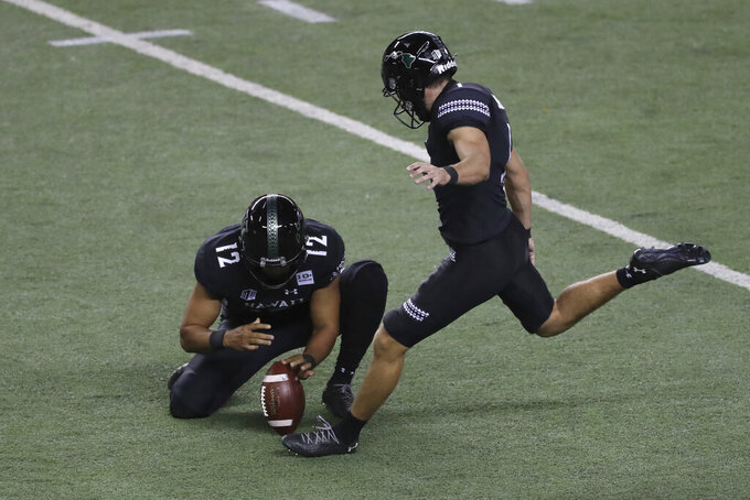 Hawaii's Matthew Shipley kicks a field goal against Boise State from the hold of Stan Gaudion (12) during the first quarter of an NCAA college football game Saturday, Nov. 21, 2020, in Honolulu. (AP Photo/Marco Garcia)