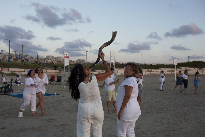 A woman holds a shofar before the start of a Tashlich ceremony, on the beach in Tel Aviv, Israel, Tuesday, Sept. 14, 2021. Tashlich, which means 'to cast away' in Hebrew, is the practice by which Jews go to a large flowing body of water and symbolically 'throw away' their sins by throwing a piece of bread, or similar food, into the water before the Jewish holiday of Yom Kippur, the holiest day in the Jewish year which starts at sundown Wednesday. (AP Photo/Maya Alleruzzo)