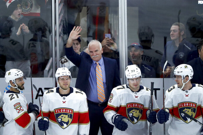 Florida Panthers head coach and former Chicago Blackhawks coach, Joel Quenneville acknowledges the crowds applause during the first period of an NHL hockey game between the Blackhawks and Panthers, marking Quenneville's return as a head coach Tuesday, Jan. 21, 2020, in Chicago. (AP Photo/Charles Rex Arbogast)
