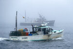 FILE -In this Wednesday, July 25, 2018 file photo, lobster fishing boats head out to sea on a foggy morning off South Portland, Maine. The federal government is working on new rules designed to reduce risk to endangered North Atlantic right whales, which can become entangled in ropes that connect to lobster and crab traps in the ocean. Early indications show that the changes required by the rules could be significant. (AP Photo/Robert F. Bukaty)