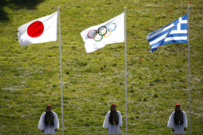FILE - In this Thursday, March 12, 2020, file photo, Greek Evzones guards stand next to Japan, Olympic and Greece flags, from left, during the flame lighting ceremony at the closed Ancient Olympia site, birthplace of the ancient Olympics in southern Greece. U.S. President Donald Trump's suggestion to postpone the Tokyo Olympics for a year because of the spreading virus was immediately shot down by Japan's Olympic Minister Seiko Hashimoto. (AP Photo/Yorgos Karahalis, File)