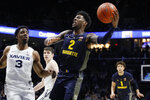 Marquette's Sacar Anim (2) shoots against Xavier's Quentin Goodin (3) during the second half of an NCAA college basketball game Wednesday, Jan. 29, 2020, in Cincinnati. (AP Photo/John Minchillo)