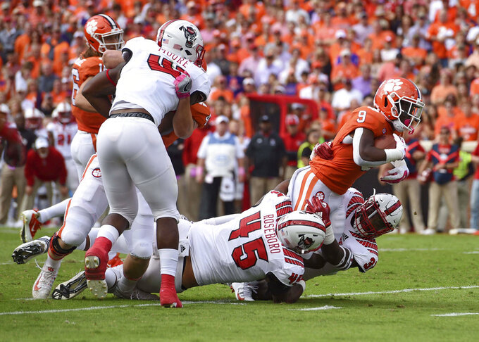 Clemson's Travis Etienne (9) rushes while defended by North Carolina State's Darian Roseboro (45) and James Smith-Williams during the first half of an NCAA college football game Saturday, Oct. 20, 2018, in Clemson, S.C. (AP Photo/Richard Shiro)