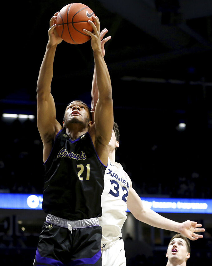 Western Carolina guard Marcus Thomas (21) rebounds the ball over Xavier forward Zach Freemantle (32) during the first half of an NCAA college basketball game, Wednesday, Dec. 18, 2019 in Cincinnati. (Kareem Elgazzar/The Cincinnati Enquirer via AP)