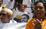 A woman holds an image of jailed opposition lawmaker and outspoken critic of President Nicolas Maduro, Juan Requesens, as she chants with others in support of the opposition controlled National Assembly, in Caracas, Venezuela, Thursday, May 16, 2019. Diplomatic efforts aimed at resolving Venezuela's crisis accelerated on Thursday as the government and opposition sent envoys to negotiate in Norway, though the two sides' mutual mistrust and differences on key issues could prevent any quick solution. (AP Photo/Martin Mejia)