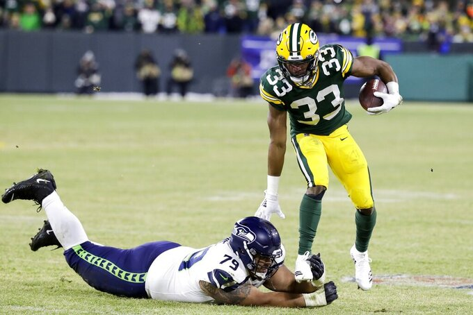 Green Bay Packers' Aaron Jones runs past Seattle Seahawks' Bryan Mone during the first half of an NFL divisional playoff football game Sunday, Jan. 12, 2020, in Green Bay, Wis. (AP Photo/Darron Cummings)