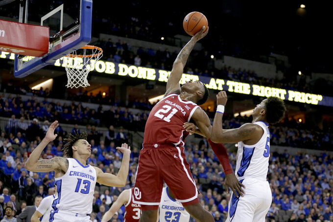 Oklahoma's Kristian Doolittle (21) grabs a rebound between Creighton's Christian Bishop (13) and Ty-Shon Alexander (5) during the first half of an NCAA college basketball game in Omaha, Neb., Tuesday, Dec. 17, 2019. (AP Photo/Nati Harnik)