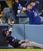 FILE - In this Oct. 16, 2018, file photo, Milwaukee Brewers' Christian Yelich can't catch a foul ball hit by Los Angeles Dodgers' Brian Dozier during the eighth inning of Game 4 of the National League Championship Series baseball game in Los Angeles. The photo was part of a series of images by photographer Mark J. Terrill which won the Thomas V. diLustro best portfolio award for 2018 given out by the Associated Press Sports Editors during their annual winter meeting in in Lake Buena Vista, Fla. (AP Photo/Mark J. Terrill, File)