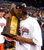 FILE - In this April 7, 2003, file photo, Syracuse's Carmelo Anthony kisses the trophy after winning the championship game 81-78 against Kansas at the NCAA college basketball Final Four in New Orleans. With no Final Four on tap this weekend thanks to the coronavirus, we instead put together a list of the greatest one-and-done players ever. Anthony Davis and Syracuse's Carmelo Anthony top our list after leading their teams to national tiles their lone season in college. (AP Photo/Ed Reinke, File)