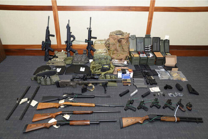 "FILE - This undated file image provided by the Maryland U.S. District Attorney's Office shows a photo of firearms and ammunition that was in the motion for detention pending trial in the case against Coast Guard lieutenant Christopher Hasson, accused of stockpiling guns and targeting Supreme Court justices, prominent Democrats and TV journalists. Hasson has asked a federal appeals court to let him withdraw his guilty plea or else throw out his sentence of more than 13 years in prison. In a court filing Monday, June 8, 2020 a defense attorney argued that Christopher Hasson's 160-month prison term was roughly four times longer than sentencing guidelines would have called for if U.S. District Judge George Hazel had not mistakenly applied a ""terrorism enhancement"" to the sentence.  (Maryland U.S. District Attorney's Office via AP, File)"