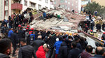 Rescue workers and people try to remove debris of a seven-story building which collapsed in Istanbul, Wednesday, Feb. 6, 2019. A seven-story building collapsed in Istanbul on Wednesday, killing at least one person and trapping several others inside the rubble, Turkish media reports said. (DHA via AP)