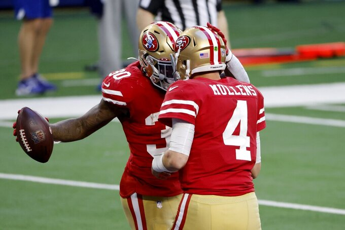San Francisco 49ers running back Jeff Wilson Jr. (30) and quarterback Nick Mullens (4) celebrate Wilson's touchdown run in the second half of an NFL football game against the Dallas Cowboys in Arlington, Texas, Sunday, Dec. 20, 2020. (AP Photo/Ron Jenkins)