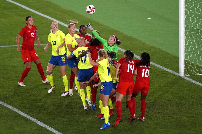 Canada's goalkeeper Stephanie Labbe, right, blocks a shot during the women's final soccer match against Sweden at the 2020 Summer Olympics, Friday, Aug. 6, 2021, in Yokohama, Japan. (AP Photo/Kiichiro Sato)