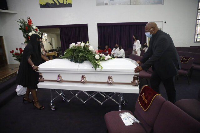 Candy Boyd, left, owner of Boyd Funeral Home, is helped as she brings in the body of Lydia Nunez, who died from COVID-19, during a funeral service at the Metropolitan Baptist Church Tuesday, July 21, 2020, in Los Angeles. When people began dying from the coronavirus in the United States, for a few weeks funeral home owner Boyd declined to receive the remains of such patients. (AP Photo/Marcio Jose Sanchez)