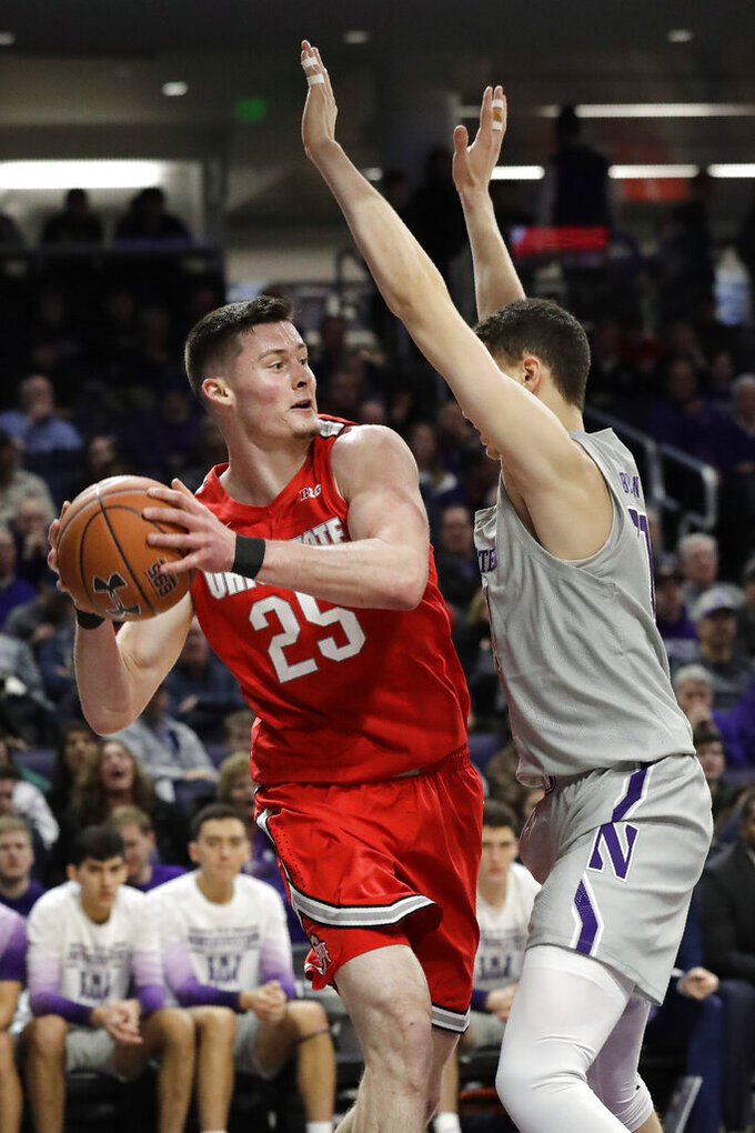 Ohio State forward Kyle Young, left, looks to pass as Northwestern forward Robbie Beran guards during the first half of an NCAA college basketball game in Evanston, Ill., Sunday, Jan. 26, 2020. (AP Photo/Nam Y. Huh)