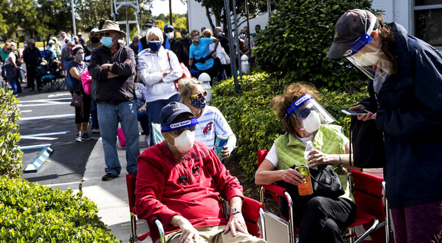 Joel and Susan Pittelman, from Naples, Fla., wait in line to receive COVID-19 vaccines on Tuesday, Dec. 29, 2020, at East County Regional Library in Lehigh Acres, Fla. (Andrew West /The News-Press via AP)